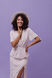 Curly brunette dark-skinned woman in white polka dot dress and wide-brimmed hat smiles widely on purple background.