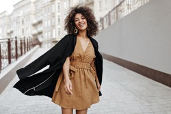Curly brunette woman in brown dress and black coat walks outside. Dark-skinned lady smiles and moves outdoors.