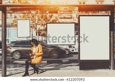 Curly brunette woman in sunglasses and yellow coat working on her digital tablet while sitting and waiting bus inside of glass city bus stop, with several blank mock-up banners around her