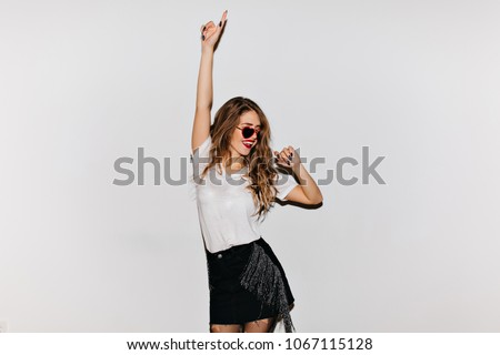 Curly brunette woman in sunglasses looking away while dancing on white background. Enthusiastic girl in black skirt posing with hand up in studio and laughing.