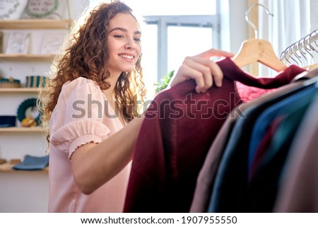 curly caucasian woman choosing 100 percent organic cotton wear in modern eco-friendly showroom, alone. she is smiling while looking at rack of clothes