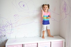 Curly cute little baby girl drawing with crayon color on the wall. Works of child