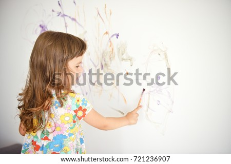 Curly cute little toddler girl painting with paints color and brush on the wall. Works of child #721236907