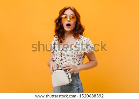Curly girl in sunglasses confusedly looks into camera and holds small white bag #1520688392