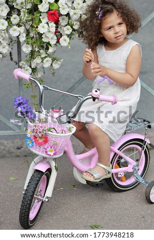 curly girl with a bicycle on a city street with flowers. High quality photo