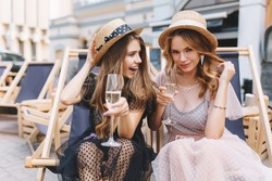 Curly girl with charming smile in elegant earrings gladly posing while her friend drink champagne. Outdoor portrait of cute ladies having fun outside relaxing on summer chairs with cold beverage.