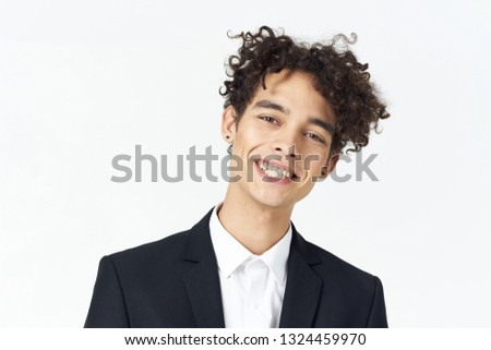 Curly guy in a shirt and jacket is smiling at the camera, cropped look                           #1324459970