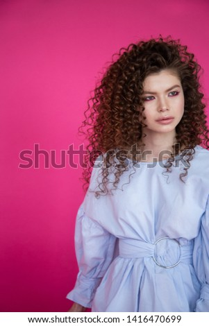 Curly hair girl in blue blouse on pink background. Fashion model with curly hair. Beautiful young girl with curly hair. Curly hair girl on pink background. #1416470699