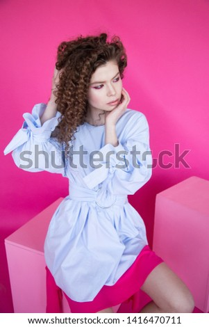 Curly hair girl in blue blouse on pink background. Fashion model with curly hair. Beautiful young girl with curly hair. Curly hair girl on pink background.