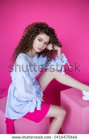 Curly hair girl in blue blouse on pink background. Fashion model with curly hair sitting on cube. Beautiful young girl with curly hair. Curly hair girl on pink background.