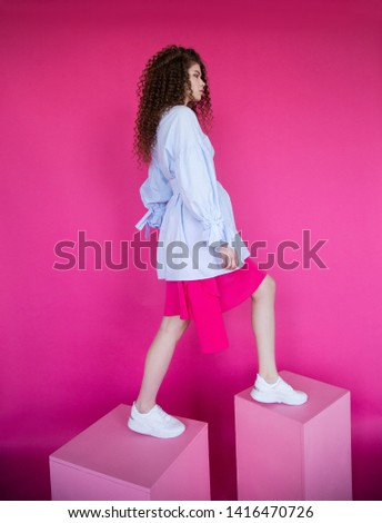 Curly hair girl in blue blouse on pink background. Fashion model with curly hair stepping on cubes. Beautiful young girl with curly hair. Curly hair girl on pink background.