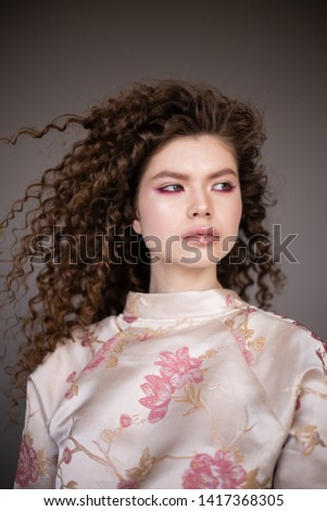 Curly hair girl in jacket with sakura print. Fashion model with curly hair on grey background. Beautiful young woman with curly hair.
