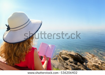 Curly hair woman reading a book against sea horizon.