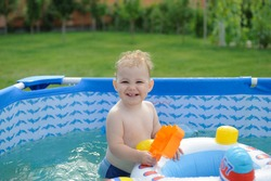 Curly haired blonde girl in swimming pool at the backyard