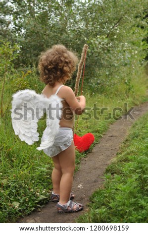 curly haired child with wings shoots from a bow in red heart.Valentine's day concept #1280698159