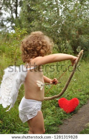 curly haired child with wings shoots from a bow in red heart.Valentine's day concept #1281319828