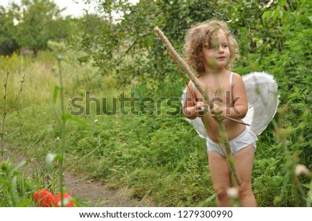 curly haired child with wings shoots from a bow in red heart.Valentine's day concept. Soft selective Focus #1279300990