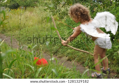 curly haired child with wings shoots from a bow in red heart.Valentine's day concept. Soft selective Focus #1281329182