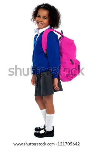 Curly haired elementary school girl carrying pink backpack on shoulders.