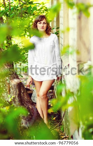 curly-haired girl with bare legs in a white shirt standing next to abandoned buildings around green foliage