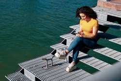 Curly-haired hipster girl sitting on metal stairs is using a smartphone on a lake dock