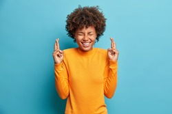 Curly haired positive Afro American woman closes eyes and crosses fingers hopes for better wears orange jumper poses against blue background smiles broadly. Agitated female makes wish poses indoor