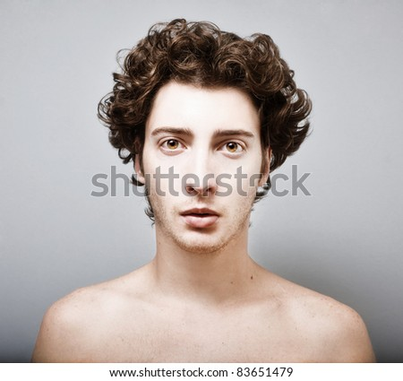 Curly haired young man on gray background with pensive expression.