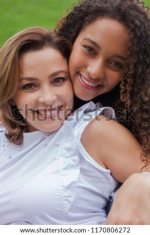 Curly haired young woman smiles at the camera with a mature woman who is lying on her. #1170806272
