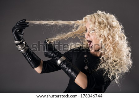 curly hairstyle blonde in black, woman hairs loss, coloring problem, beautiful girl holding hairs and surprised, over gray background