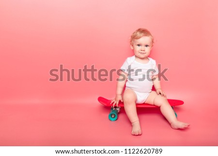 curly little baby girl child with red skateboard over pink background. concept sport.