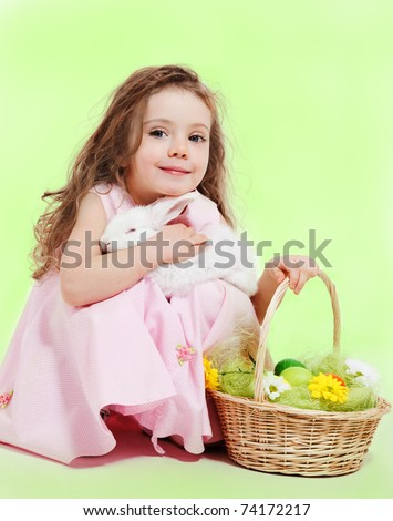 Curly little girl with Easter basket and white bunny in hands