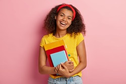 Curly lovely college student has positive expression, prepares for exam and reads literature, wears yellow t shirt, poses over pink background. Good emotions, ethnicity and studying concept.