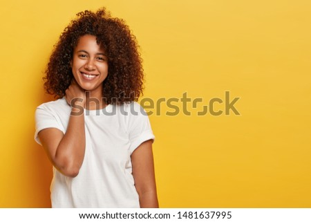 Curly lovely female touches neck, grins joyfully, has flirty look, enjoys spare time, wears casual white t shirt, talks casually with someone, expresses positive emotions isolated on yellow background