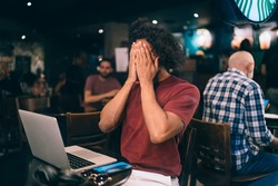 Curly male programmer feeling shame during remote working and web projecting have online mistake on laptop computer, skilled millennial blogger shy during netbook network browsing in cafe interior