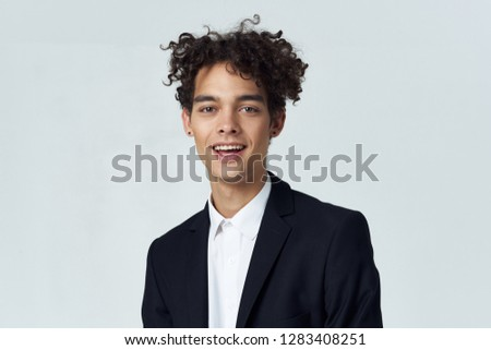 Curly man in shirt and jacket on a light background        #1283408251