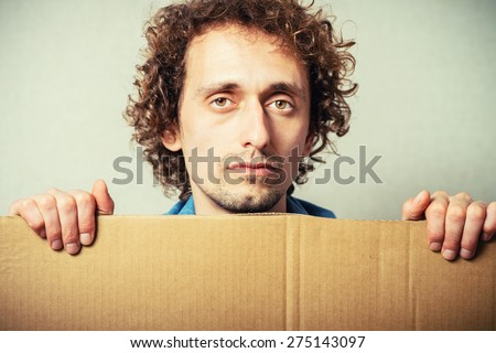 Curly man with empty cardboard. On a gray background.