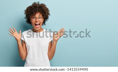 Curly optimistic woman raises palms from joy, happy to receive awesome present from someone, shouts loudly, dressed in casual white t shirt, isolated on blue background. Excited Afro female yells