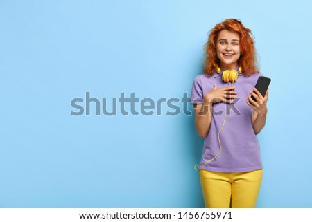Curly red haired woman touches to read daring message, feels touched and impressed, keeps hand on chest, has perfect mood, wears purple t shirt and yellow trousers, reads funny story on social media