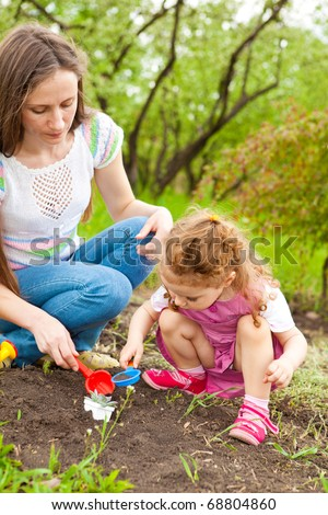 Curly toddler daughter helping her mom in the garden