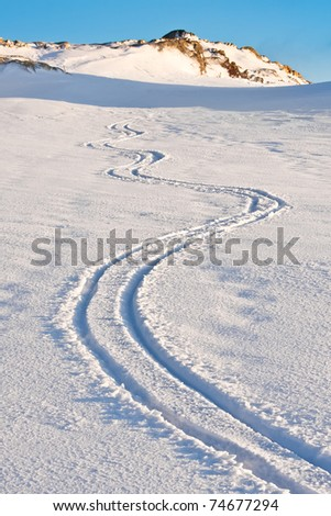 Curly trace of skis on the snow in the mountains of Antarctica