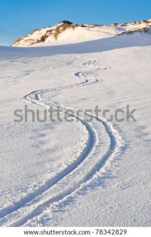 Curly trace of skis on the snow in the mountains of Antarctica - stock photo