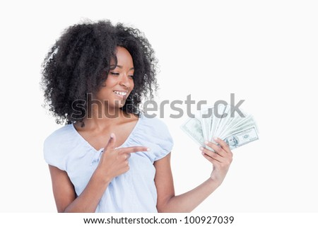 Curly woman closing eyes while pointing her finger on a fan of dollar notes