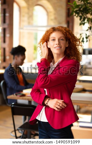 Curly woman. Curly woman with brassy hair standing near her colleague in spacious office