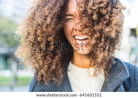 Curly woman laughing and shaking head. Smiling mixed race woman with curls having fun. Smart casual dress. Lifestyle and hairstyle concepts