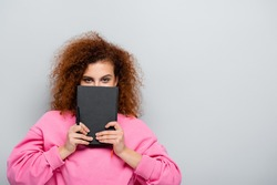 curly woman obscuring face with notebook while looking at camera isolated on grey