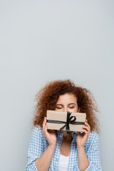 curly woman with closed eyes obscuring face with gift box isolated on grey