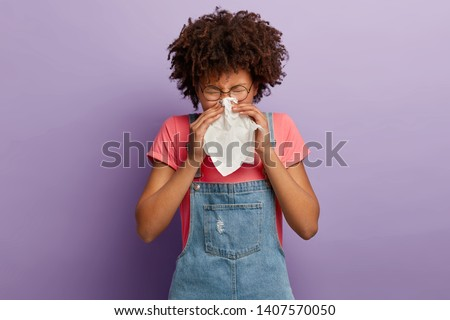Curly young female feels unwell, blows nose in white tissue, suffers from running nose, cold symptoms or allergy, sneezes very often, wears round spectacles, casual t shirt and denim sarafan
