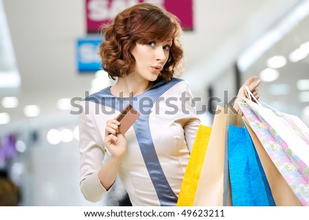 Curly young woman in shop with a credit card