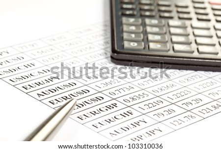Currency cross-rate table, calculator and a pen; concept of financial analysis