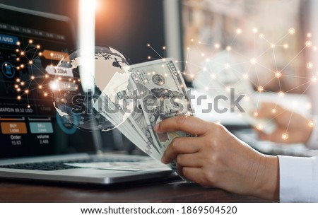 Currency exchange, financial and banking in global networking business concept. Businessman holding banknote, analysing stock market growth and making profit on currency converter exchange.